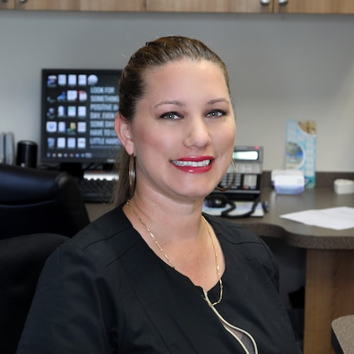 A staff member greeting people with a smile at one of the top dentists in Palm Beach Gardens