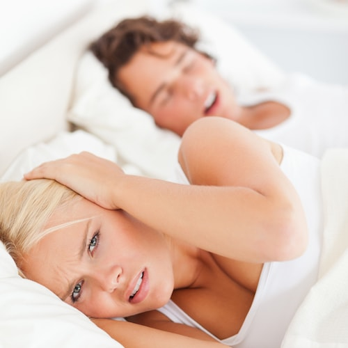 A couple trying to sleep but in need of Restorative Dentistry Palm Beach Gardens to prevent snoring