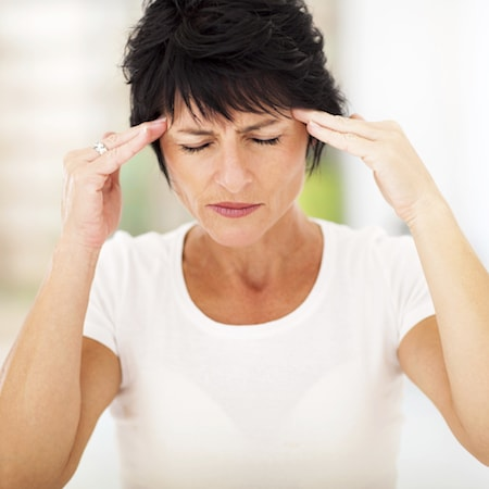 A woman suffering from TMJ, a service provided by your dentist in Palm Beach Gardens FL