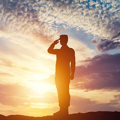 A veteran soldier saluting as the sun sets - As part of our dental savings plan, we offer discounts to veterans