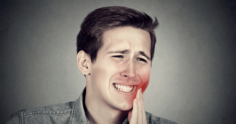 A young man holding the side of his mouth in pain needing a dental emergency consultation
